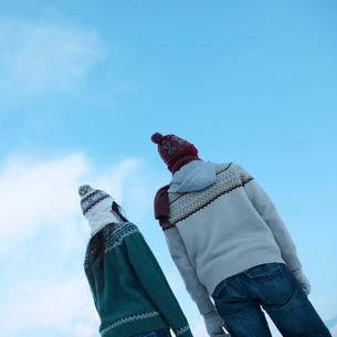 青空の下、寄り添うカップルの後ろ姿の写真素材 [FYI03913257]