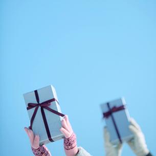 青空に持ち上げたプレゼントの写真素材 [FYI03913270]