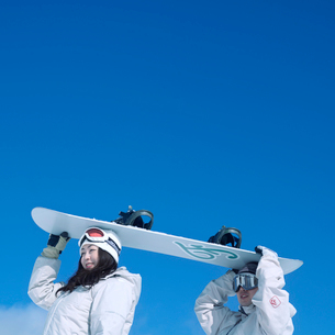 スノーボードを運ぶカップルの写真素材 [FYI03913339]