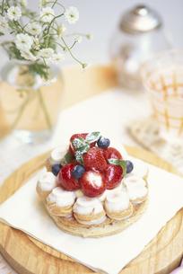 苺とブルーベリーをのせたパイと花瓶に白小花等の写真素材 [FYI03913713]