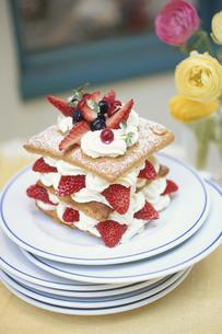 重ねたお皿にのせたナポレオンパイケーキ・ラナンキュラスの写真素材 [FYI03913719]