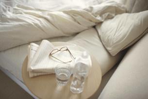 新聞と眼鏡を置いたサイドテーブルとベットの写真素材 [FYI03913854]