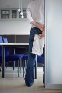 新聞を後ろ手に持ち立つ女性の写真素材 [FYI03913867]