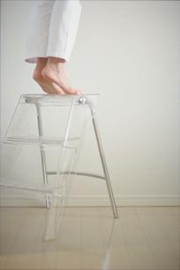 脚立の上でつま先立ちする女性の写真素材 [FYI03913870]
