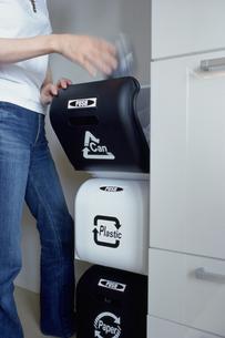 分別ゴミ箱に空き缶を捨てる女性の写真素材 [FYI03913871]