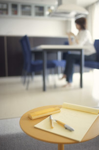 メモとペンのあるテーブル越しにデスクに座る女性の写真素材 [FYI03913876]
