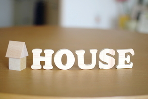 テーブルに置かれた家の積み木とHOUSE文字の写真素材 [FYI03913908]