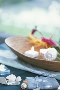 皿の上のキャンドルや貝殻や花の写真素材 [FYI03914678]
