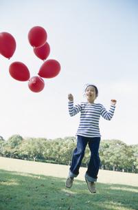 赤い風船を持って飛ぶ女の子の写真素材 [FYI03915008]