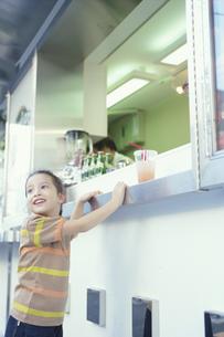 ジューススタンドのカウンターに立つ女の子の写真素材 [FYI03915018]