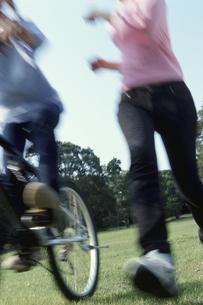 公園を走る女性と自転車で走る人の写真素材 [FYI03915047]