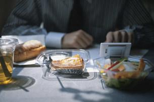 軽食を摂りながら携帯電話を見る男性の手元の写真素材 [FYI03915683]