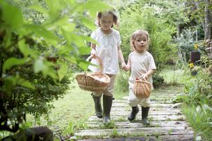 カゴを持って歩く姉妹の写真素材 [FYI03915792]
