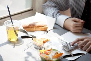 携帯電話を見ながら軽食を摂る男性の手元の写真素材 [FYI03915812]