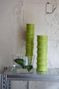 壁際のシェルフの上の葉を活けた花瓶等の写真素材 [FYI03915826]