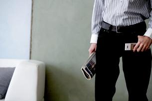 壁際で雑誌と携帯電話を持った男性の写真素材 [FYI03915827]