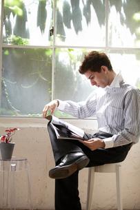 窓辺のスツールに座り雑誌を見る外国人男性の写真素材 [FYI03915835]