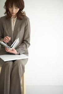 椅子に座って手帳を見る女性の写真素材 [FYI03915983]