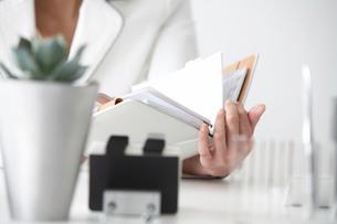 手帳を見る女性の手元の写真素材 [FYI03915997]