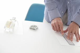 定規を使って紙を切る男性の手元の写真素材 [FYI03916019]