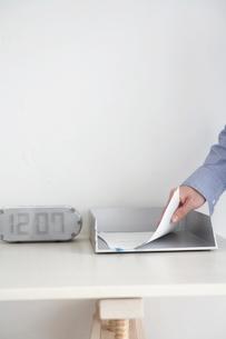 デスクの上の書類を取る男性の写真素材 [FYI03916031]