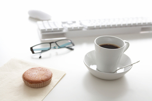デスクの上のキーボードとパンケーキとコーヒーの写真素材 [FYI03916034]