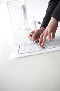 定規を使って書類に線を引く女性の手元の写真素材 [FYI03916072]