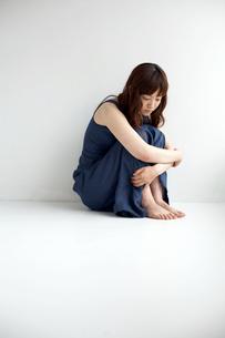 壁を背にして座る女性の写真素材 [FYI03916156]