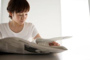 テーブルで新聞を見る女性の写真素材 [FYI03916159]