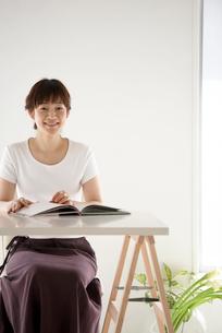 イスに座って正面を向く女性の写真素材 [FYI03916161]