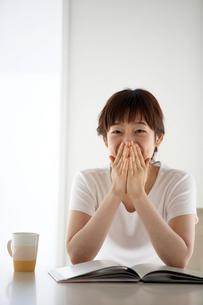テーブル上で微笑む女性の写真素材 [FYI03916164]