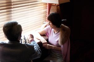 室内でチェスをする男性と女性の写真素材 [FYI03916382]