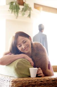 ソファでくつろぐ女性と後姿の男性の写真素材 [FYI03916388]