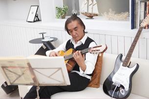 ソファに座り楽譜を見ながらギターを弾く男性の写真素材 [FYI03916437]