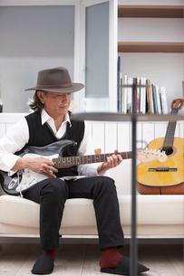 ソファに座り帽子を被ってギターを弾く男性の写真素材 [FYI03916439]