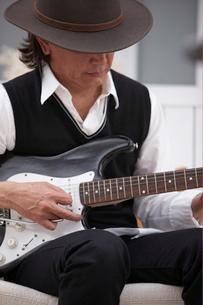ソファに座り帽子を被ってギターを弾く男性の写真素材 [FYI03916440]
