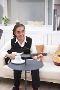 ソファに座りギターを持つ男性の写真素材 [FYI03916441]