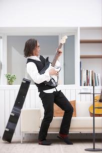 立ってギターを弾く男性の写真素材 [FYI03916442]