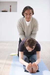 男性に背中を押されてストレッチする女性の写真素材 [FYI03916452]
