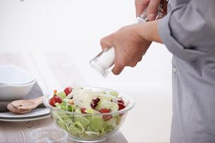 サラダに塩をふる手元の写真素材 [FYI03916470]