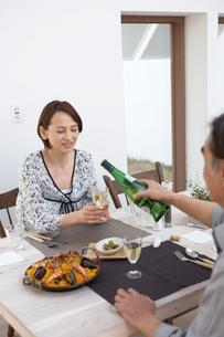 飲み物を注ぎ食事の準備をする夫婦の写真素材 [FYI03916480]