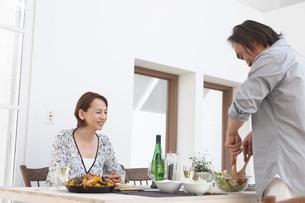 サラダを取り分け食事の準備をする夫婦の写真素材 [FYI03916483]