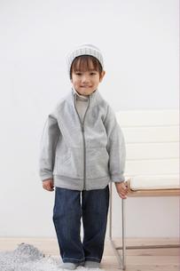 帽子を被ってイスのそばに立つ男の子の写真素材 [FYI03916499]
