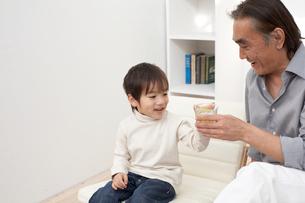 グラスに入ったジュースと水で乾杯する祖父と孫の写真素材 [FYI03916503]
