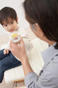 グラスに入ったジュースと水で乾杯する祖父と孫の写真素材 [FYI03916504]