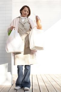 両腕に買い物袋を下げて立っている女性の写真素材 [FYI03916506]
