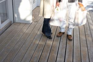 買い物袋やバッグを持って立っている夫婦の足元の写真素材 [FYI03916508]