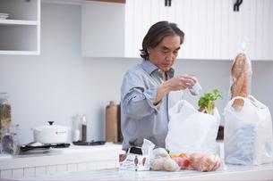 キッチンで買い物袋から食材を取り出す男性の写真素材 [FYI03916510]