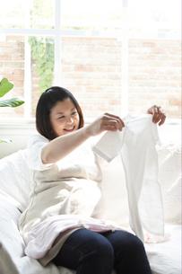 ベビー服を眺める妊婦の写真素材 [FYI03916533]