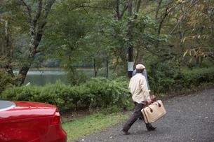 トランクを持った男性と赤い車の写真素材 [FYI03916581]